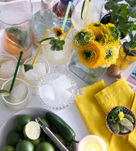 Table with margarita ingredients and flowers