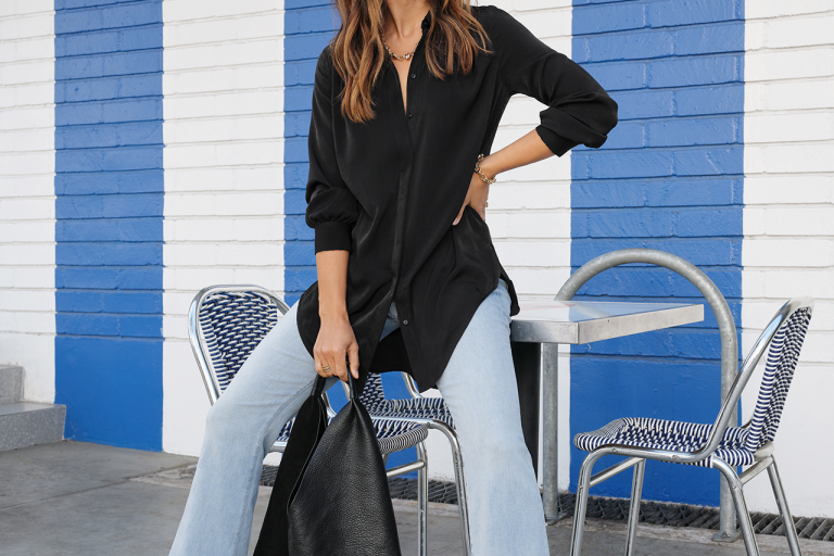 A woman models Express jeans, top and bag.